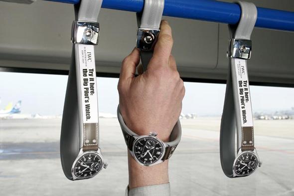 Exemple de guerilla marketing : promotion d'une montre de pilote sur les poignées d'un bus d'aéroport.